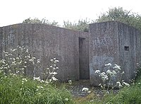 A rear view of an eastern Command Type pillbox showing the huge blast wall covering the entrance.