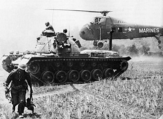 Operation Starlite - A MAG-16 helicopter evacuates casualties, while a Marine M48 Patton tank stands guard