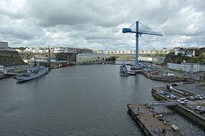 Brest Arsenal - La Penfeld vue vers l'amont depuis le pont de Recouvrance. De gauche à droite : l'entrée des bassins de Pontaniou, barrée par le batardeau mis en place à l'occasion des travaux de modernisation de 2006 ; les ateliers du plateau des Capucins ; la direction de DCNS ; le pont Tréhouart ; la grande grue ; l'entrée du bassin Tourville