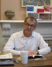 grey haired man in white shirt with glasses seated at table reading from a book