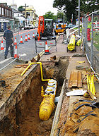 Polyethylene gas main being laid in a trench.
