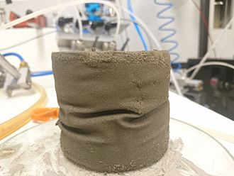 Triaxial shear test - Post-liquefaction testing. The fine sand specimen was liquefied during CU cycles and recovered with CD cycles many times. The wrinkles formed due to extreme volume change imposed by iterating between CU liquefaction and draining. In liquefied state sample become soft enough to imprint thin latex. During CD cycles - stiff enough to preserve the imprinted pattern. No bulging or shear rupture is present despite numerous instances of pure plastic yielding.
