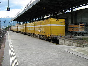 Swiss Post - Postal wagons at the postal sorting facility in Sion, Switzerland. Mail between regional cities is transported by rail, to be delivered by postal bus, vans and cycles at a local level.