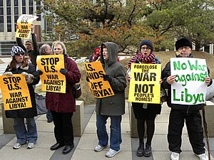 US domestic reactions to the 2011 military intervention in Libya - Demonstrators in Minneapolis, Minnesota, show placards on March 21, 2011, to protest against the military intervention in Libya by the U.S.