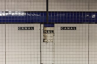 Canal Street (IND Eighth Avenue Line) - A section of the platform wall showing three layers of tile, including the original IND tilework.