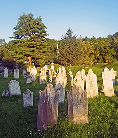 A cemetery; grave stones in the foreground in staggered, irregular rows; behind them grass covered mounds of dead; an American flag in the background along a tree line.