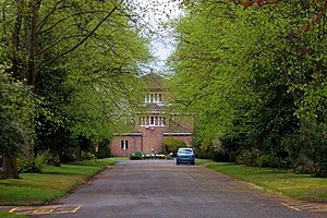 Robin Hood Cemetery - The cemetery chapel was built in 1931 for the then Solihull Urban District Council and enlarged in 1958 with the addition of a crematorium. This view from the east along the avenue of ancient Arden oaks, supplemented by more recent holly bushes, shows the earlier part of the building.
