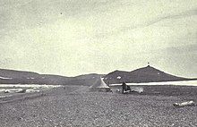 A conical tent stands on a desolate stretch of beach, with a range of low hills in the background.