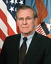man in business suit, American flag in background