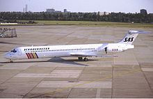 A medium jetliner with an all-white body andcolored stripes
