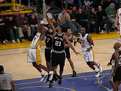 Duncan (#21) attempts to block a shot in a game against the Los Angeles Lakers.