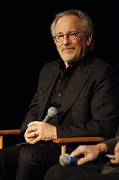Stephen Spielberg sits on a chair with a microphone in his hand