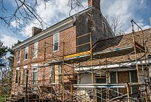 Old brick house with scaffolding in front