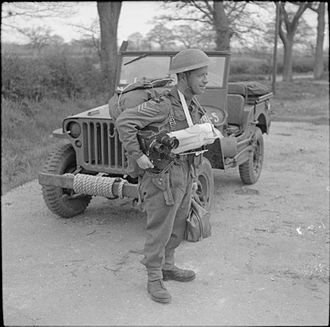 Army Film and Photographic Unit - Sergeant W A Greenhalgh, Army Film and Photographic Unit, with his jeep during Exercise 'Fabius', Hayling Island,  Hampshire, 6 May 1944 (IWM H38276)