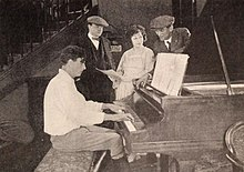 Milton Sills playing the piano for Arthur Somers Roche, Ora Carew, and director Phil Rosen
