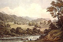 A wooded river valley surrounded by mountains, with a distant grand house and lawns on the far slope
