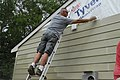 U.S. Army 1st Sgt. Benton Gil measures the length of a house before installing its sidings while volunteering for the Habitat for Humanity at Edinburgh, Ind., Aug 110812-A-VC802-003.jpg