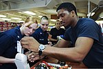 U.S. Navy Ship's Serviceman Seaman Marcus Lee, right, rings up Sailors' purchases in the ship's store aboard the aircraft carrier USS Nimitz (CVN 68) June 20, 2013, in the Gulf of Oman 130620-N-AZ866-459.jpg