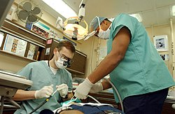 US Navy 030124-N-1328C-510-mararmea dentisto traktas pacientojn sur ship.jpg