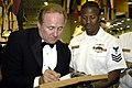 US Navy 050820-N-7281D-048 Michael Reagan, son of former President Ronald Reagan and radio talk show host, signs a chief selectee's charge-book at the Taste of Freedom dinner hosted by the Navy League aboard the Nimitz-class ai.jpg