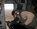 US Navy 071208-M-5865P-001 U.S. Marine Corps Sgt. Scott R. Johnson, an aerial observer with Marine Heavy Helicopter Squadron 361, scans terrain during an aero scout mission over the Al Anbar province.jpg