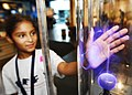 US Navy 090714-N-2456S-049 Nine year old, Kaitlynn Walker places her hand on the glass casing of a plasma ball at the Hampton Roads Naval Museum.jpg