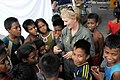 US Navy 090826-N-9689V-016 Donna Willard, wife of U.S. Pacific Fleet commander Adm. Robert F. Willard, speaks with children at Betio Sports Complex during a Pacific Partnership 2009 medical civic action project.jpg