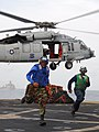 US Navy 091106-N-5538K-223 Aviation Boatswain's Mate (Handling) Airman Derek C. Townsend and Aviation Support Equipment Technician Airman Apprentice Quatin F. Robinson run clear OF an MH-60S Sea Hawk helicopter.jpg