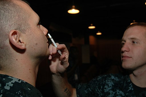 US Navy 110907-N-KE148-015 Hospital Corpsman Christopher Bradburry administers an influenza vaccine via nasal injection to Hospital Corpsman 3rd Cl