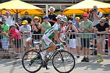 Photographie d'un coureur cycliste, habillé en en vert en blanc, vu de profil.