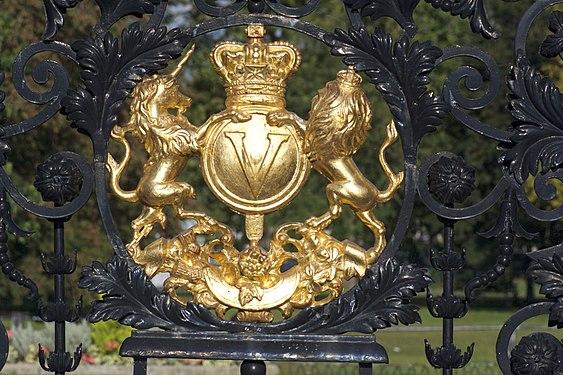 Verse of Elizabeth II Coat Of Arms in golden color on a black metal gate
