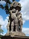 Gebeeldhouwde groep van putto-figuurtjes, die een zonnewijzer dragen
