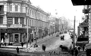 Old photo of city streets, with horse-drawn wagons