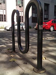 Ground-level view of a black-painted metal square tube bent into a curved M shape and bolted to concrete by a road. In the background are two cars parked in front of a long building.