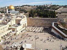 Uma grande área aberta com pessoas delimitadas por muros de pedra antigos.  Para a esquerda é uma mesquita com grande cúpula dourada.