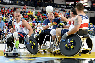 Invictus Games - Three American defenders knock the ball away from an Australian player during a wheelchair rugby pool match between the United States and Australia at the 2014 Invictus Games