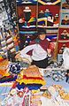Woman with drop spindle in a colorful market stall with colorful products in Equador.jpg