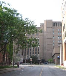 An image of the road leading up to a large, multi-story brick building. A tree is in front.