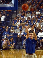 A man, wearing a blue shirt and brown pants, is shooting a basketball on a basketball court.