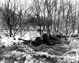 Battle of Lanzerath Ridge - Soldiers man a 30 caliber heavy machine gun in a foxhole during the Battle of the Bulge.