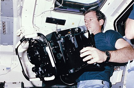 STS 41-C mission specialist Terry J. Hart, holds a 70-pound IMAX camera in the mid deck of the space shuttle Challenger in 1984. 635715main 84HC188 full.jpg