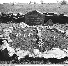A grave site marked with white rocks and two headstones, in front of a low rock wall