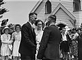 A bride and groom with confetti on their heads standing outside a church on wedding day (AM 88048-1).jpg