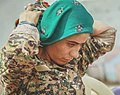 A soldier with the YPJ ties a scarf around her head.jpg