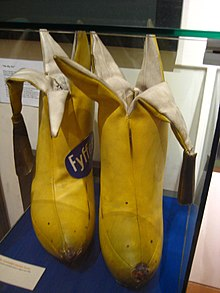 Two yellow bananas tailor-made in cloth with the tops peeled and the cloth skin hanging down.