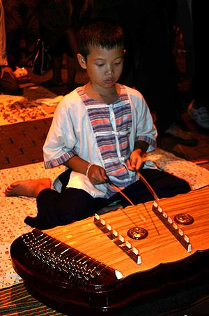 Traditional Thai musical instruments - A boy playing a khim (hammered dulcimer)