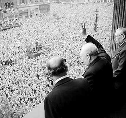 Churchill waving the Victory sign to the crowd in Whitehall on the day he broadcast to the nation that the war with Germany had been won, 8 May 1945. Ernest Bevin stands to his right. Churchill waves to crowds.jpg