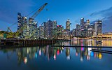 Crane and skylines of the Central Business District reflecting in the water at blue hour in Singapore.jpg