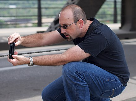 A man takes a photo with a smartphone, holding it somewhat awkwardly, as the form factor of a phone is not optimized for use as a camera D'Arcy Norman, Professional iPhone Photographer (4728847341).jpg