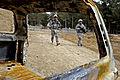 Defense.gov News Photo 110119-F-2185F-021 - U.S. Army Pfc. Carlos Ortiz left and Spc. Kevin Vo walk past a burned-out car during a trip to a village near Shahr-e Safa Afghanistan on Jan.jpg